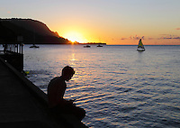 Silhouetted by the sunset, a fisherman patiently sits on the  Hanalei Pier at Hanalei Bay, Kaua'i.