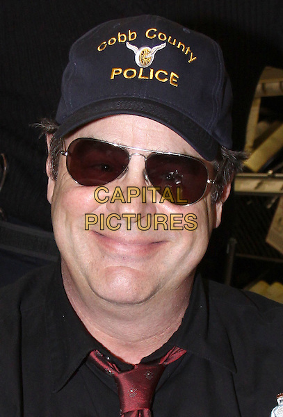 DAN AYKROYD.Signs his line of signature wine and Crystal Head vodka held at World of Liquors, Elizabeth, New Jersey, USA, .08 April 2009..half length black cap sunglasses aviators red tie police shirt .CAP/ADM/PZ.©Paul Zimmerman/Admedia/Capital Pictures