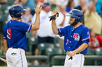 Round Rock Express outfielder Bryan Petersen (7) is greeted at home by teammate Adam Rosales (9) during the Pacific Coast League baseball game against the Sacramento River Cats on June 19, 2014 at the Dell Diamond in Round Rock, Texas. The Express defeated the River Cats 7-1. (Andrew Woolley/Four Seam Images)