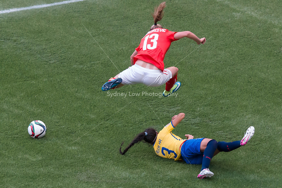 June 12, 2015: Ana Maria CRNOGORCEVIC of Switzerland jumps over Nancy AGUILAR of Ecuador during a Group C match at the FIFA Women's World Cup Canada 2015 between Switzerland and Ecuador at BC Place Stadium on 12 June 2015 in Vancouver, Canada. Switzerland won 10-1. Sydney Low/AsteriskImages