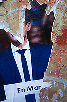 "France. Ile de France. Paris. Partially torn campaign poster of French presidential election candidate Emmanuel Macron for the centrist party ""En Marche"". 21.04.17 © 2017 Didier Ruef"