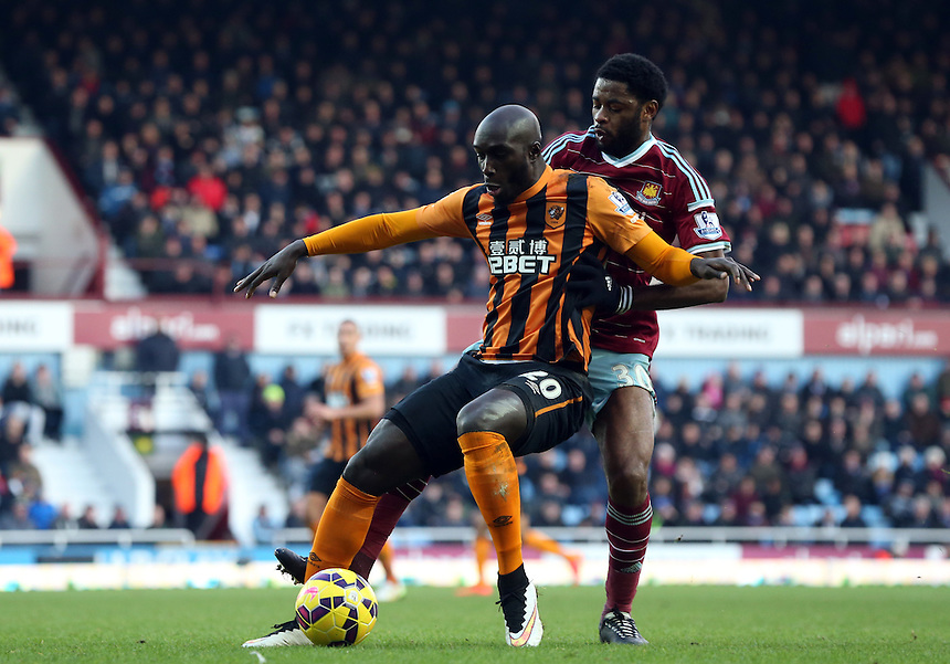 Hull City's Yannick Sagbounder pressure from  West Ham United's Alex Song<br /> Photographer Kieran Galvin/CameraSport<br /> <br /> Football - Barclays Premiership - West Ham United v Hull City - Sunday 18th January 2015 - Boleyn Ground - London<br /> <br /> &copy; CameraSport - 43 Linden Ave. Countesthorpe. Leicester. England. LE8 5PG - Tel: +44 (0) 116 277 4147 - admin@camerasport.com - www.camerasport.com