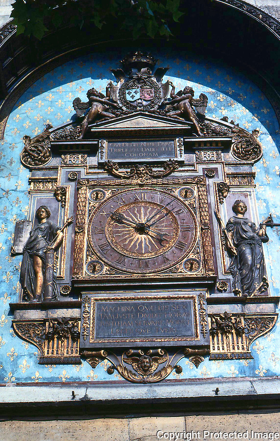 Visual Arts: Paris-- Conciergerie--Tour de L'Horloge, 1370.  The first public clock installed in Paris.  The carvings on the face, 16th century.  Photo '90.