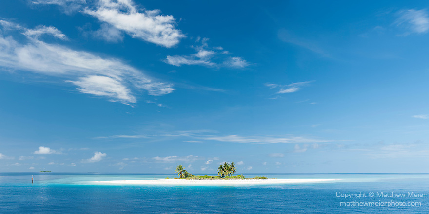 Mattidhoo Island, Huvadhoo Atoll, Maldives; a panoramic view of a remote, deserted island in the Indian Ocean, with palm trees and white sand beaches, surrounded by a shallow coral reef
