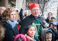 """Timothy Cardinal Dolan of the Archdiocese of NY, right, with  Linda Mirels, board chair of the UJA-Federation, left,  promoting the 3rd annual """"Feeding our Neighbors: An Interfaith Response"""" in front of St. Patrick'sCathedral in New York on Sunday, January 19. 2014. The campaign is an interfaith effort between Catholic and Jewish social service organizations to collect food donations to re-fill the sorely depleted food pantries, meal programs  and soup kitchens that serve those in need.  (© Richard  B. Levine)"""