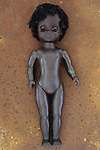 Modern plastic black girl doll slightly scratched and soiled lying on rusty metal sheet