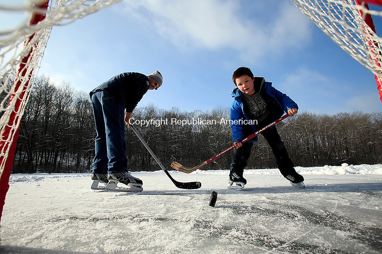 Middlebury, CT-01, January 2010-010110CM08 --  It was a father-son New Years moment on Turtle Pond in Middlebury Friday afternoon.  Sam Hamilton, 10 shoots the puck past his father, Alex, both of Middlebury, while playing ice hockey.  It's nice that we have our own pond to skate and play hockey on. It's almost as if it's our own private rink.  A lot of places you have to pay, and you can't play hockey on. This works out great. Alex Hamilton said.    Christopher Massa Republican-American