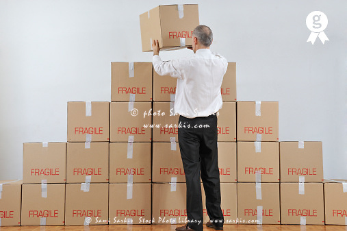 Businessman arranging a boxes pyramid (Licence this image exclusively with Getty: http://www.gettyimages.com/detail/109862336 )