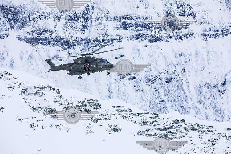 A British Merlin helicopter fly over a mountain ridge during practice in the Arctic, near Bardufoss, Norway. <br /> <br /> In 2019 the Arctic exercise Clockwork passed 50 years of training in Norway, and now has a permanent base within the Norwegian Air Force base at Bardufoss. <br /> <br /> 845 Naval Air Squadron is a squadron of the Royal Navy's Fleet Air Arm. Part of the Commando Helicopter Force, it is a specialist amphibious unit operating the Leonardo Commando Merlin Mk3 helicopter and provides troop transport and load lifting support to 3 Commando Brigade Royal Marines.<br /> <br /> ©Fredrik Naumann/Felix Features