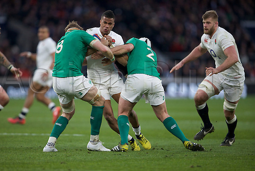 27.02.2016. Twickenham, London, England. RBS Six Nations Championships. England versus Ireland. England wing Anthony Watson is tackled by Ireland number 8 Jamie Heaslip and Ireland hooker Rory Best.