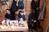 Hugh Neff, Jeff King and Lance Mackey get something to drink and warm up inside the cook shack at the Cripple checkpoint 1/2 way into the race during the 2010 Iditarod