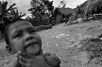 A young Nukak boy stands in front of the shacks in a refugee settlement close to San Jose del Guaviare, Colombia, 4 September 2009. The Nukak Maku people, nomadic hunter-gatherers from Amazonia, were violently driven out of the jungle by the Colombian guerilla and paramilitary squads. Now, roughly cut off their original tribal lifestyle, they stuck between worlds. They learn from the (mainly Christian) aid workers to use clothes, to listen to the radio, to beg for money. Although their digestion suffer, they love to eat sweets, cookies and other western food. They have hunted out all the animals around and now there is nothing left for them. Nukak can not return to the jungle, their world has already passed through an irreversible change.