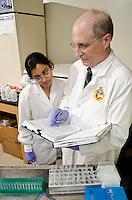 Dr. Lakshmi Narayanan (PhD), assists Dr. Cody Coyne in lab.