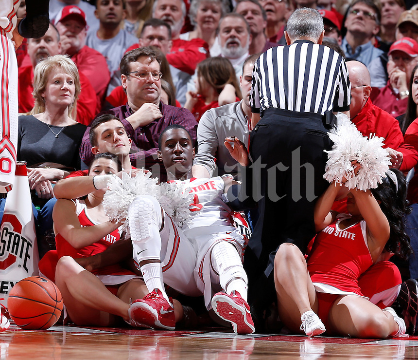 Ohio State Buckeyes guard Shannon Scott (3) takes a tumble into the cheerleaders after chasing a loose ball during the first half of the NCAA men's basketball game between the Ohio State Buckeyes and the Minnesota Golden Gophers at Value City Arena in Columbus, Ohio, on Saturday, Feb. 22, 2014. At the end of the first half, Minnesota led Ohio State, 28-18. (Columbus Dispatch/Sam Greene)