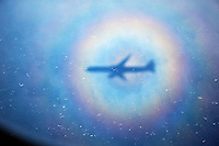 Shadow of an aeroplane surrounded by a rainbow halo against the sea.