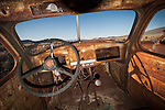 Landscape through the windshield of a rusted and abandoned pickup truck in a roadside-field, Nev.