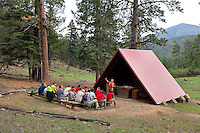 Photo story of Philmont Scout Ranch in Cimarron, New Mexico, taken during a Boy Scout Troop backpack trip in the summer of 2013. Photo is part of a comprehensive picture package which shows in-depth photography of a BSA Ventures crew on a trek.  In this photo Father Donald Hummel leads a worship service at an outdoor church for BSA Venture Crews passing through the Cimarroncito Camp in the backcountry at Philmont Scout Ranch.   <br /> <br /> <br /> The  Photo by travel photograph: PatrickschneiderPhoto.com