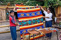 Santa Ana del Valle, Oaxaca, Mexico.  Weaver Ernesto Martinez Cruz (left) Displaying one of his Carpets.