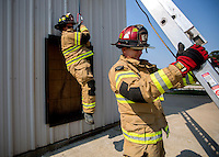NWA Democrat-Gazette/JASON IVESTER <br /> Cpt. Michael Braswell secures the ladder as Fire Fighter Doug Earp is lowered on Wednesday, Aug. 26, 2015, at the Rogers Fire Department's training center. Firefighters with Ladder 1, Engine 2, Engine 6 and Medic 1 were at the center going through quarterly training.