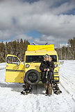 USA, Wyoming, Yellowstone National Park, a tourist stands in front of a Yellowstone Snowcoach on the road in the Lower Geyser Basin