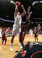 Virginia forward Anthony Gill (13) shoots over Virginia Tech guard Ben Emelogu (15) during the game Saturday in Charlottesville, VA. Virginia won 65-45.