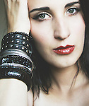 Soft focus close-up portrait of a young woman with pale skin and green eyes resting her head on her hand and arm with a lot of different bracelets, staring at the camera.