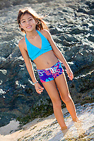 A smiling young girl stands along the shore at a windy beach on the North Shore of O'ahu.