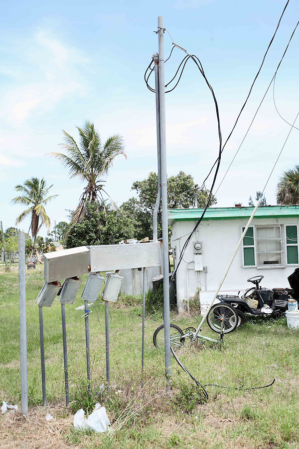 Disconnected electric meters are all that remain on empty land that was once a trailer park community.  A small shack abuts the former park's property where its owner is now the sole resident.
