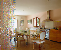 The kitchen doubles as a dining room with a glass-topped dining table and gilt-framed chairs