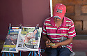 25/02/16 <br /> <br /> A newspaper vendor, wearing an 'I Love Jesus' hat counts money as a large breasted woman is displayed on one of his newspapers in Granada, Nicaragua.<br /> <br /> <br /> All Rights Reserved: F Stop Press Ltd. +44(0)1335 418365   +44 (0)7765 242650 www.fstoppress.com
