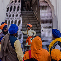 ANANDPUR SAHIB, INDIA - March 06, 2015: An Indian Sikh youth talks with family members during a religious procession to mark Hola Mohalla at the Guru Dwara Sri Kesgarh Sahib temple at Sri Anandpur Sahib, during Hola Mohalla celebrations on March 06, 2015 in Anandpur Sahib, India. Hola Mahalla or simply Hola is a Sikh event, which takes place on the first of the lunar month of Chet, which usually falls in March, and sometimes coincides with the Sikh New Year. It was started by Guru Gobind Singh the tenth Sikh guru in 1701 AD. Hola Mohalla is a three day Sikh festival, in which Nihang Sikh 'warriors' perform Gatka (mock encounters with real weapons), tent pegging and bareback horse-riding.<br /> <br /> Daniel Berehulak for The New York Times