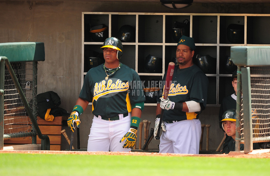 Mar. 19, 2012; Phoenix, AZ, USA; Oakland Athletics outfielder Yoenis Cespedes (left) and designated hitter Manny Ramirez in the dugout during fourth inning against the Arizona Diamondbacks during a spring training game at Phoenix Municipal Stadium.  Mandatory Credit: Mark J. Rebilas-.