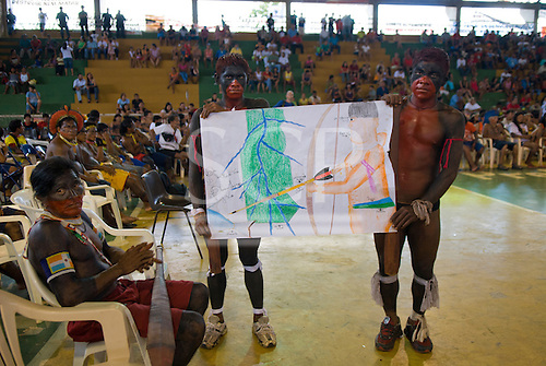"Altamira, Brazil. ""Xingu Vivo Para Sempre"" protest meeting about the proposed Belo Monte hydroeletric dam and other dams on the Xingu river and its tributaries. Two Ikpeng Indian carrying a drawing of the Xingu and a warrior."