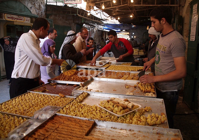 Palestinian vendors sell sweets outside their shop in the old city of the West Bank city of Hebron on November 15, 2010, ahead of the Muslim holiday of Eid al-Adha or Feast of the Sacrifice, which marks the end of the annual hajj or pilgrimage to Mecca and is celebrated in remembrance of Abraham's readiness to sacrifice his son to God. Photo by Najeh Hashlamoun