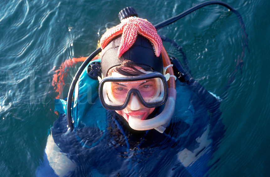 Scuba diver at surface with starfish on head.