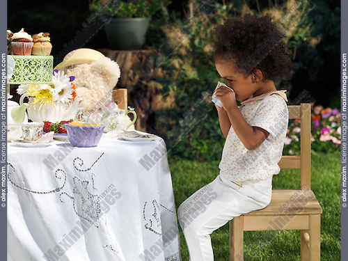Little girl drinking tea at an outdoor summer party