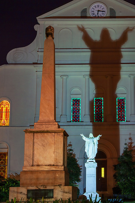 Light casting a shadow of Mary behind the St. Louis Cathedral at night.
