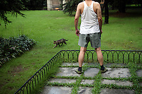 A man and a cat in a park near West Lake in Hangzhou, one of the most visited tourists sites in China. Zhejiang Province. China. 2010