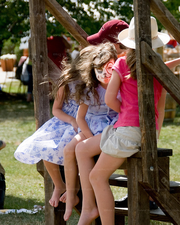 Three girls with festively painted faces wait for the hay ride to come around, on the lawn at Breaux Vineyards' annual Key West Fest.