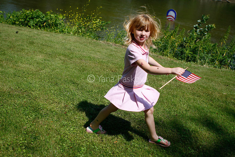 A little girl runs across the lawn past the campaign logo of Democratic Presidential hopeful Barack Obama (D-IL), as he campaigns in Manchester, IA, on July 14, 2007.