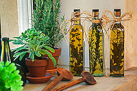 Herb vinegars (Sages, Rosemary) on kitchen window sill with pots of fresh herbs