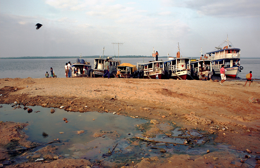 Passengers gather around Amazon river boats at the port city of Manaus. Docked agaings dry season mud, the boats are still the principle mode of trabsportation in the region.
