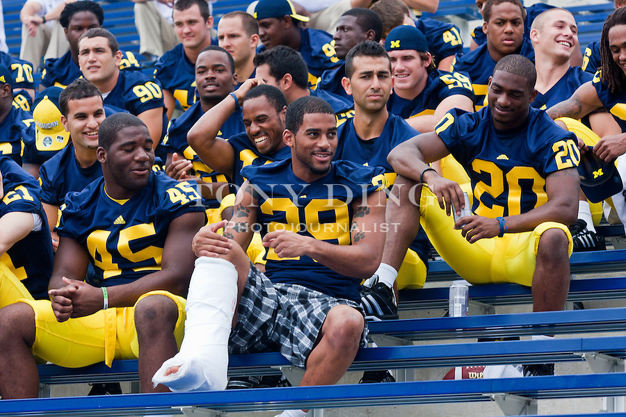 Michigan safety Troy Woolfolk (29), in a cast, sits with teammates waiting for a group photo, at the annual NCAA college football media day, Sunday, Aug. 22, 2010, in Ann Arbor, Mich. Woolfolk injured his leg in fall camp and is likely out for the season. (AP Photo/Tony Ding)