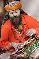Pashupatinath, Nepal.  Sadhu (Holy Man) at Nepal's Holiest Hindu Temple, Playing an Accordian-like Instrument.