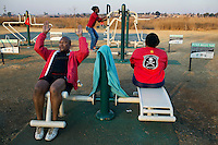 SOWETO, SOUTH AFRICA JULY 7: Sowetans use one of the new outdoor gyms on July 7, 2014 in Soweto, South Africa. The residents of Soweto has seen massive investment such as shopping malls, parks, outdoor gyms in the township. Soweto today is a mix of old housing and newly constructed townhouses. The population in Soweto is estimated to be around one million people. A new hungry black middle-class is growing steadily. Many residents work in Johannesburg but the last years many shopping malls have been built, and people are starting to spend their money in Soweto. (Photo by: Per-Anders Pettersson)