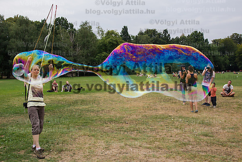 Woman blows a giant soap bubble during a soap bubble day in a public park in Budapest, Hungary on August 25, 2013. ATTILA VOLGYI