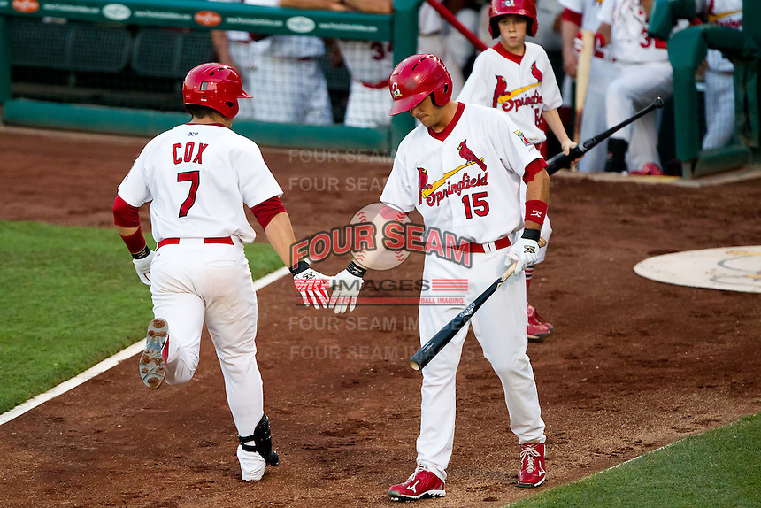 Eric Duncan (15) of the Springfield Cardinals high-fives Zack Cox (7) after he scored during a game against the Tulsa Drillers at Hammons Field on July 20, 2011 in Springfield, Missouri. Springfield defeated Tulsa 12-1. (David Welker / Four Seam Images)