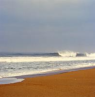 A wave breaks as it hits the empty beach