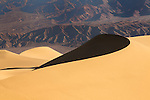 Sloping s-curve of sand dune in front of mountain.  Taken at the Mesquite Dunes in Death Valley