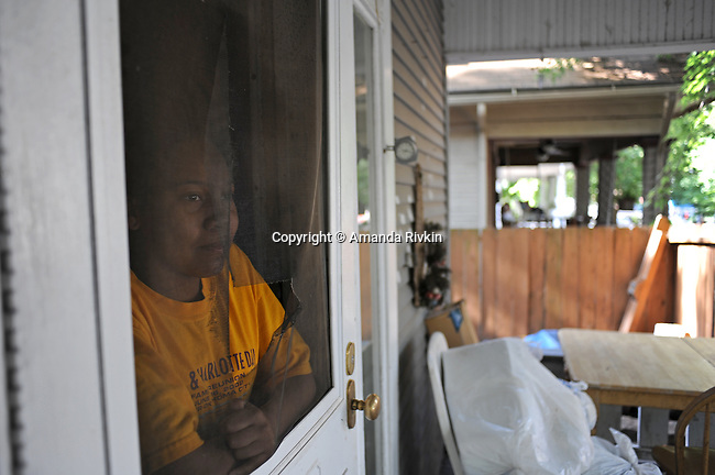 Kevonna Murdock, 13, watches from her front door as family, friends, supporters and members of the media arrive outside the College Hill United Methodist Church before the funeral for assassinated abortion doctor George Tiller in Wichita, Kansas on June 6, 2009.  Tiller was gunned down while serving as an usher at his church last Sunday by Scott Roeder, who is now in custody, in a political crime with reverberations across the region and the country; Tiller's Wichita clinic had previously served as a culture wars flashpoint in the 1990s.